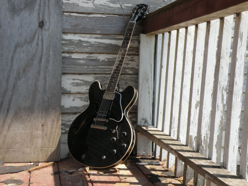 Guitar propped up in corner railing